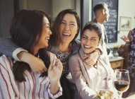 Enthusiastic, smiling women friends hugging and drinking at bar — Photo de stock