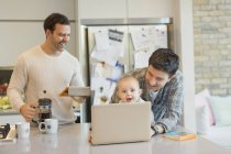 Male gay parents and baby son using laptop and digital tablet in kitchen — Stock Photo