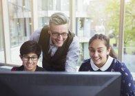Enseignant de sexe masculin et les étudiants recherchant à l'ordinateur dans la bibliothèque — Photo de stock