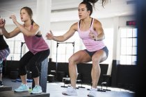 Determined young women doing jump squats in exercise class — Stock Photo