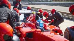 Ravitaillement à remplacement de pneus sur la voiture d'une course formule dans la voie des stands — Photo de stock