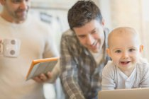 Portrait cute baby son with male gay parents using digital tablet — Stock Photo