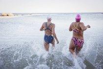 Вид сзади женского активного пловцов, работает на океан на открытом воздухе — стоковое фото