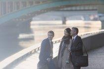 Gente de negocios sonriente hablando en el waterfront urbano - foto de stock