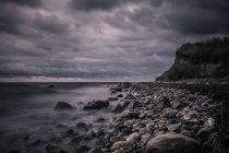Спокійна порід на океані пляжу нижче бурхлива, хмарність хмари, Bisserup, Данія — стокове фото