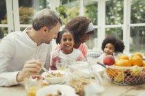 Портрет, улыбаясь многоэтнического молодой семьи едят завтрак за столом — стоковое фото