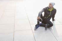 Smiling male runner resting, holding headphones and looking away — Stock Photo