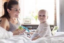 Portrait mère et fille jouant sur le lit — Photo de stock