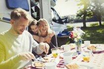 Glückliche Familie umarmt und Essen Frühstück draußen sonnige Wohnmobil — Stockfoto