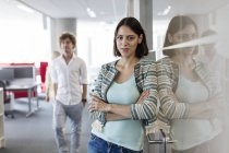 Portrait confident businesswoman leaning on glass in office corridor — Stock Photo