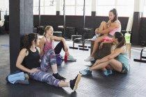 Junge Frauen reden und ruhen nach dem Training im Fitness-Studio — Stockfoto