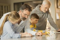 Schwule männliche Eltern helfen Kindern bei Hausaufgaben am Schalter — Stockfoto