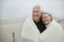 Smiling affectionate senior couple wrapped in a blanket on beach — Stock Photo