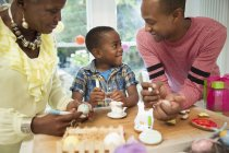 Multi-generation family decorating Easter eggs and cookies — Stock Photo