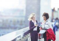 Empresárias usando tablet digital em ponte urbana — Fotografia de Stock