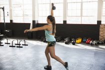 Young woman practicing lunges with kettlebell in gym — Stock Photo