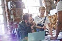 Réunion de designers souriants à l'ordinateur portable dans l'atelier — Photo de stock