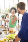 Happy family preparing meal in domestic kitchen — Stock Photo