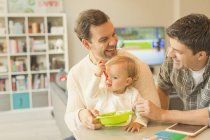 Male gay parents feeding baby son — Stock Photo