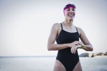 Female smiling swimmer standing at ocean outdoors — Stock Photo