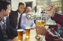 Bartender pouring beer from tap behind bar — Stock Photo