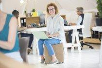 Porträt einer Frau mit Laptop im Büro — Stockfoto