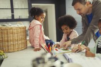 Multi-ethnic father and daughters coloring and using activity books in kitchen — Foto stock