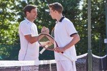 Handshaking di giocatori di tennis maschile giovane sorridente in sportività sopra rete sul tennis — Foto stock