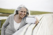 Smiling senior woman taking selfie at boardwalk ledge — Stock Photo