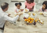 Multi-ethnic family eating breakfast at table — стоковое фото