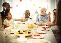 Famiglia di diverse generazioni multietnica celebra la festa di compleanno al tavolo — Foto stock