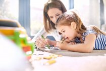 Mother and daughter coloring in coloring book with crayons — Stock Photo