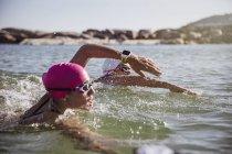 Определяется женщин открытой воде пловец с смарт-часы, купаясь в солнечном океане — стоковое фото