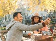 Молода пара беручи selfie з камери телефону в осінній тротуарі кафе — стокове фото