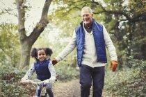 Abuelo y nieta bicicleta en el Parque otoño - foto de stock