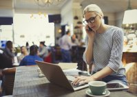 Creative businesswoman talking on cell phone and using laptop in cafe — Stock Photo