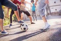 Amigos jugando al fútbol en verano calle - foto de stock