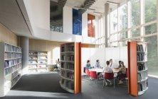 Gli uomini d'affari si riuniscono alla tavola rotonda nella biblioteca open space — Foto stock