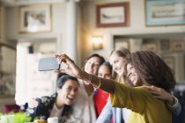 Smiling women friends taking selfie with camera phone in restaurant — Stock Photo