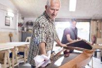 Senior man finishing, wiping wood kayak in workshop — Stock Photo