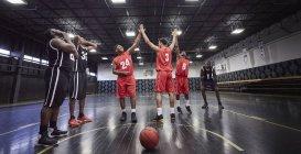 Молодые баскетболисты дают пять, празднуют на корте в гимназии — стоковое фото