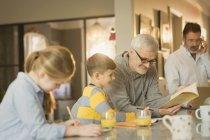 Pais de gays masculinos ajudando crianças com dever de casa no balcão — Fotografia de Stock