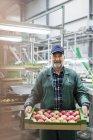 Портрет улыбающегося рабочего с коробкой яблок на заводе по переработке пищевых продуктов — стоковое фото