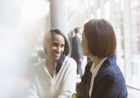Smiling businesswomen talking together at modern office — Stock Photo