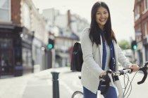 Portrait femme d'affaires souriante qui fait la navette à vélo sur une rue urbaine ensoleillée — Photo de stock