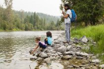 Father and daughters hiking, resting at lakeside — Stock Photo