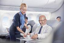 Assistente di volo che serve caffè espresso caffè all'uomo d'affari in prima classe su aereo — Foto stock