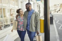 Affectionate young couple with shopping bags walking along urban storefront — Stock Photo