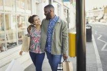 Ласкава молоді пара з сумками, гуляючи по міських магазину — стокове фото