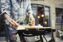Молодая женщина с рулеткой измерения древесины на патио — стоковое фото
